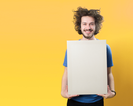 Bearded man with mustache and funny hair holding blank white board on orange  background Stock Photo