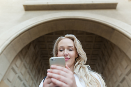 Beautiful blonde woman typing on her phone.