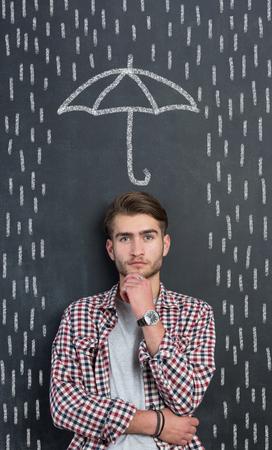 Hombre protegido por un paraguas y lluvia