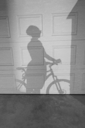 two tone: Shadow of a woman riding a bike on a textured wall. Two tonal image