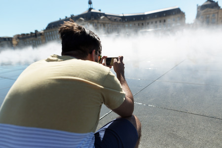 Man taking photos on his phone on main square in Bordeaux in France Stock Photo