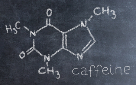 Chemical molecule structure on blackboard. Science teacher or chemistry student drawing chemical formula on blackboard in class. Nicotine, carnitine, testosterone, caffeine forumula.