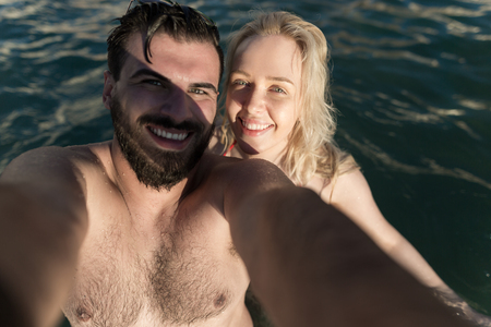 Young and beautiful couple taking selfie at the sea