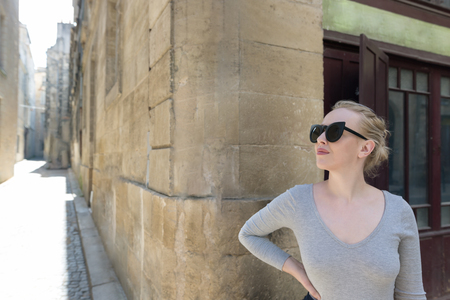 Portrait of a beautiful blonde woman with sunglassess exploring the medieval city. Tourist in France.