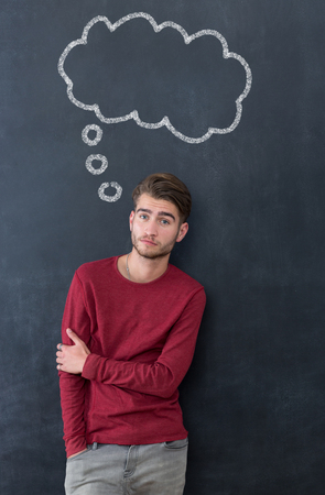 checker: Young man against the background of chalkboard thinking about something
