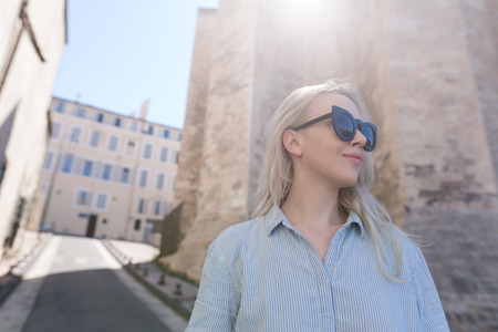 Photo of a beautiful blonde woman against the rustic church wall in France in Marseille
