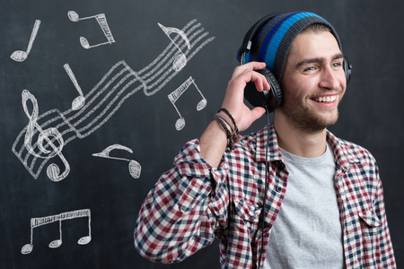 Pretty smiling young man with  listening music in headphones with musically drawings Stock Photo