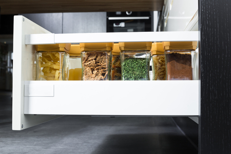 kitchen cabinets: Side view of a spices and groceries organized in a modern kitchen drawer. Kitchen design inspiration.