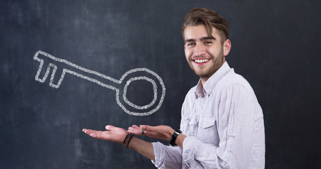 rate: Real Estate Concept. Portrait of man in front of chalkboard with house key