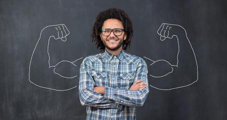 黒板に描かれた筋肉の背景に対する若者