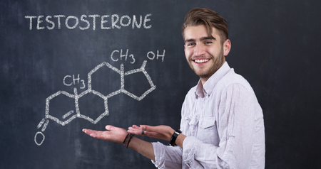 medical drawing: chemical structure of testosterone molecule drawn on chalkboard background with man in front of it Stock Photo