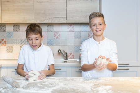 Two children having fun baking in the kitchen, Two brothers playing in kitchen
