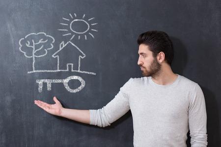 不動産の概念。家の鍵と黒板の前の男の肖像