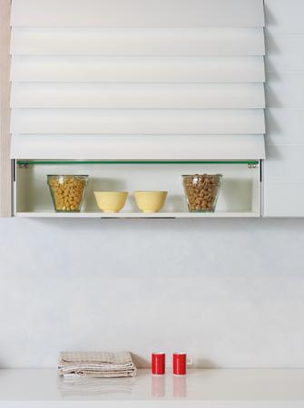 organised: Food ingredients organized on a shelf on modern kitchen countertop. White simple kitchen. Stock Photo