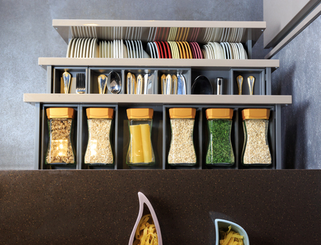 home decorating: Modern kitchen countertop with food ingredients. Top view of drawers with spices organized inside.