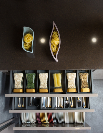Modern kitchen countertop with food ingredients. Top view of drawers with spices organized inside.
