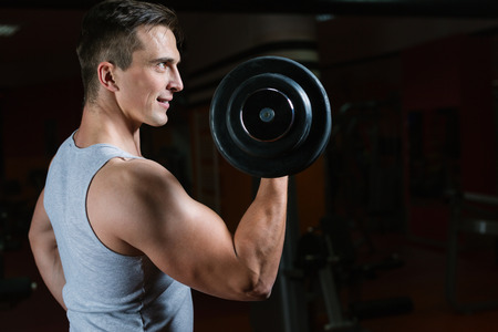 Closeup portrait of a muscular man workout with barbell at gym.  Deadlift barbells workout.