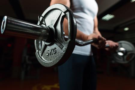 De jonge knappe Kaukasische bodybuildersportman die met een barbell in gymnastiek uitwerken, die bicepsen de opleiding doen, sluit omhoog