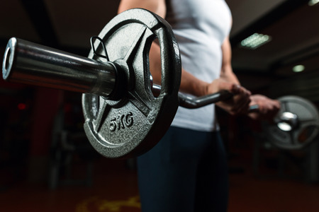 Young handsome caucasian bodybuilder sportsman working out with a barbell in gym, doing biceps training, close up
