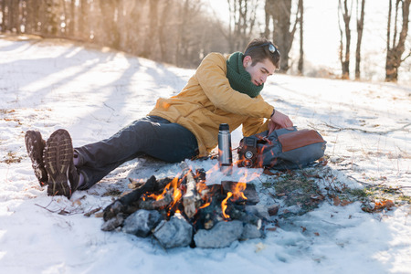 Man on mountain relaxing at campfire. Man warming his hands at winterday on his way to explore the mountains. Editorial