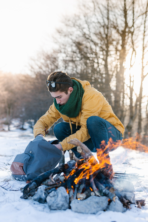 Man on mountain relaxing at campfire. Man warming his hands at winterday on his way to explore the mountains. Stock Photo