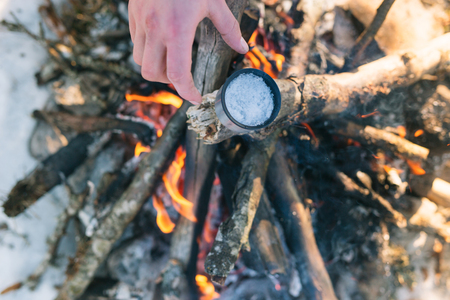 Man defreezing ice from the cup on bonfire in winter day.