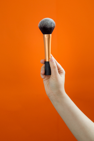 Set of makeup brushes on orange background.  Imagens