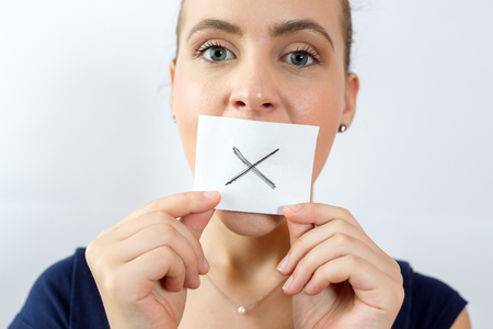 close up portrait of young attractive woman with mouth and lips sealed with white square with X sign on it.