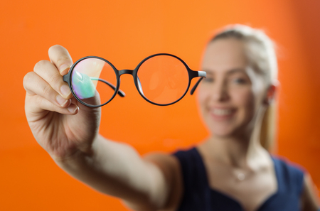 Woman showing glasses close to the camera. Blurred woman in background. Stock Photo