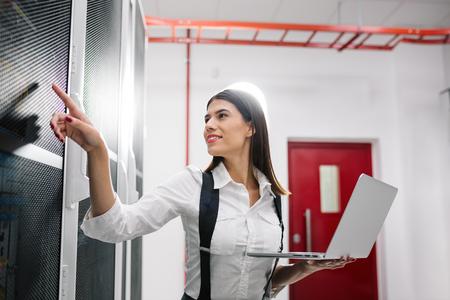 Portrait of technician working on laptop in server room