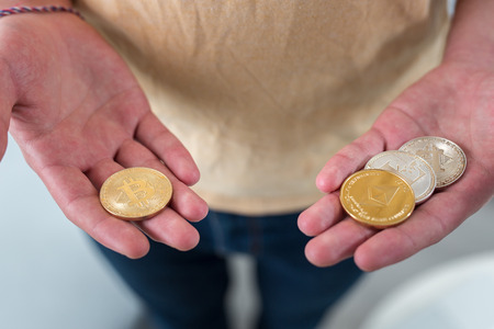 hand with a pile of bitcoins Stock Photo