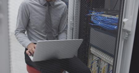 Technician performing maintenance tasks in a server room rack