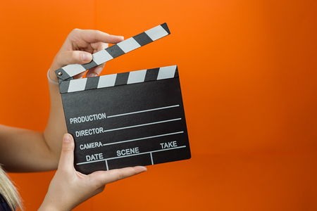 Woman holding an movie clapper in studio