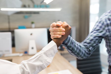 African and caucasian handshake in office having corporation success