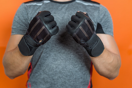Fitness man preparing gloves for lifting weights Stock Photo