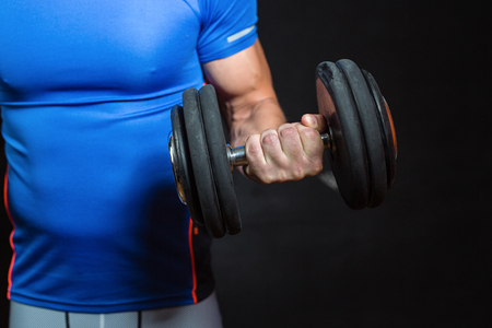 Young muscular man exercising with dumbbells on black background