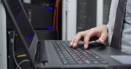 IT data specialist working on laptop on maintaining server rack
