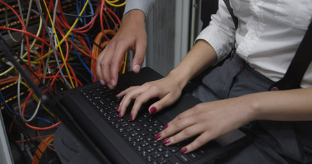 Technicians using laptop while analyzing server in server room