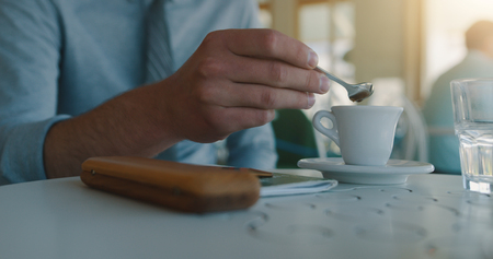 Young businessman drinking coffe before going to the office. Closeup of coffe cup. Morning light Stock Photo
