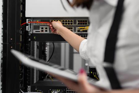 Technician examining server in server room Zdjęcie Seryjne
