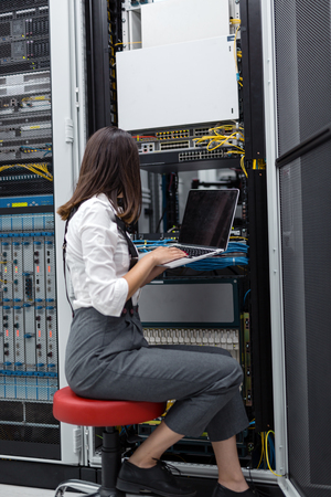 Technician apecialist woman using laptop while analyzing server in server room