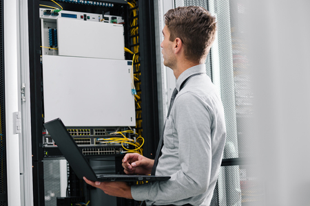 young man connecting wires in server cabinet while working with supercomputer in data center