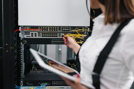 Technician examining server in server room Imagens - 119092684