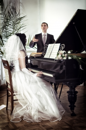 Bride plays the piano, and the groom is watching. photo