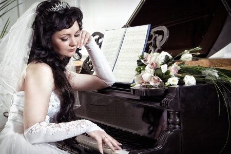 The bride looks thoughtfully at the piano photo