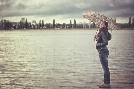 lonely girl with an umbrella in the city reservoir photo