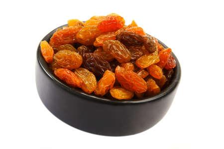 Bowl of sweet raisins on white background.