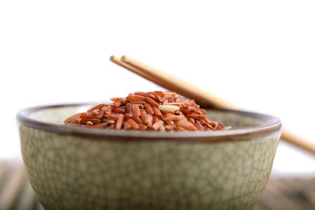 Bowl of red rice from Thailand and chopsticks.