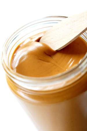 Open the peanuts butter jar. Peanut butter is excellent addition for sandwiches and desserts. Stock Photo