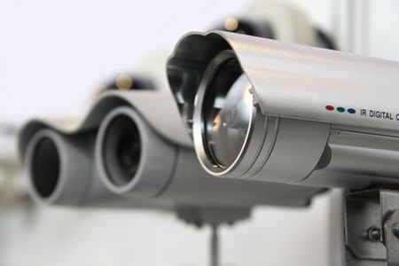 monitoring system: CCTV security cams on white wall background.